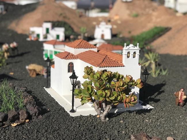"""Por su calidez y encanto como destino, la isla de Lanzarote es un destino ideal para pasar las Navidades. Si tiene pensado visitar Lanzarote durante la Navidad, le invitamos a incluir en su plan de viaje 6 ideas para pasar unas vacaciones navideñas de lo más cálidas e inolvidables. Top 6 de actividades de Navidad en Lanzarote 1. Visitar un belén tradicional Si no está muy familiarizado con las tradiciones españolas, le interesará conocer que una costumbre navideña típica en todo el país es recrear con figuritas el nacimiento de Jesús en el pesebre de Belén. Esto resulta especialmente atractivo para los niños, que se entretienen jugando con las distintas figuras del belén y decorando la escena con pinturas, papel, cartulinas y demás materiales. Belen de Lanzarote en Navidad A un nivel mayor dentro del arte de los belenes, están los que se exhiben públicamente en distintas partes de la isla de Lanzarote, muchas veces con finalidades benéficas. Existen belenes espectaculares que vale la pena visitar, como los que le mostramos a continuación: Belén de Yaiza Al norte de Lanzarote, en Yaiza, cada año van muchos visitantes a ver su increíble belén, cuya característica más llamativa es que en él se recrean a pequeña escala los lugares más representativos de esta bonita localidad de casas blancas y del resto de la isla. Al recorrer este belén de 23 metros de largo, se tiene la sensación de estar viajando por una Lanzarote en miniatura. ¡No se lo pierda! Lanzarote en Navidad Belén de Yaiza Belén de Tinajo Si normalmente los belenes son a escala pequeña, el belén de Tinajo (al oeste de la isla), ubicado junto a la Iglesia de San Roque, lo es a escala natural. Resulta impresionante ver este """"belén viviente"""", escenificado con los propios vecinos de la localidad y alguno animales como cabritillos y gallinas. ¡Todo muy auténtico! Belén de Haría En medio del conocido como Valle de las Mil Palmeras se ubica el pueblo de Haría, una parada obligada para todo aquel que visite la isla d"""